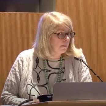 blonde woman with glasses speaking at a lecturn