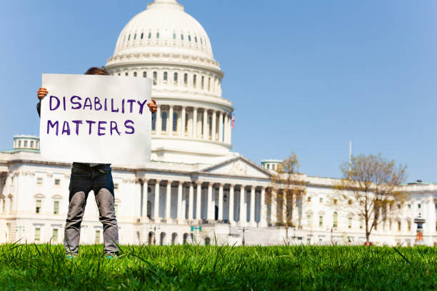 """Image of child holding up handwritten sign reading """"disability matters"""" in front of a government building"""